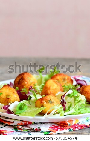 Homemade fried potato balls with pumpkin seeds served with lettuce mix and basil on a plate. Background with copy space for text. Simple and delicious potato recipe. Vertical photo