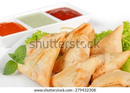 homemade fried samosas and sauces on white background - stock photo