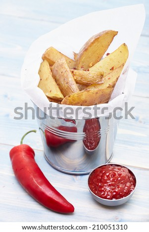 Homemade Fries in a small metal bucket with chili pepper and ketchup