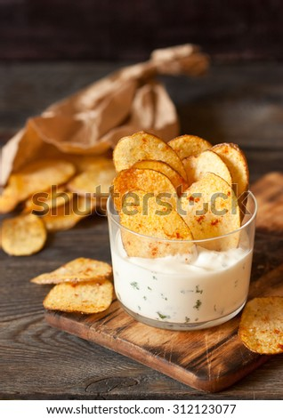 Homemade fries potato ships with dip served in glass.