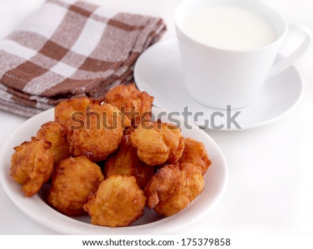 Homemade fritters and cup of milk. Traditional croatian cookies called Fritule. - stock photo