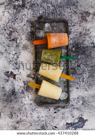Homemade frozen fruit juice or ice pop with pop stick on a tray. Top view. Rustic style. - stock photo
