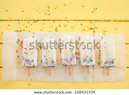 Homemade frozen vanilla popsicles with colorful sprinkles - stock photo