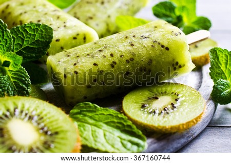Homemade fruit popsicle with kiwi and mint. Selective focus. - stock photo