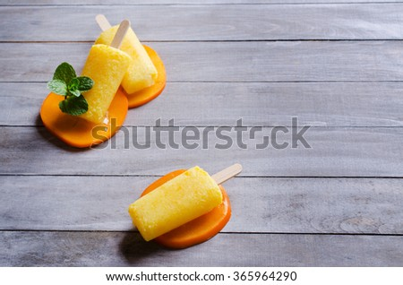 Homemade fruit popsicle with persimmon and mint. Selective focus. - stock photo