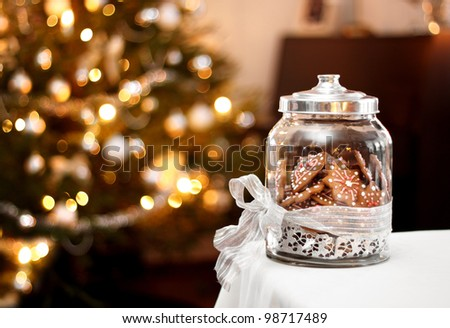 Homemade gingerbread biscuits in glass jar, Christmas background
