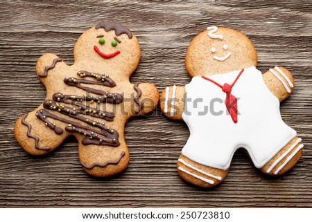 homemade gingerbread couple on wooden table - stock photo
