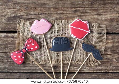 Homemade gingerbreads in the form of photobooth props (mustache, lips, the bow tie and cylinder) on the wooden table. Space for text and selective focus. - stock photo