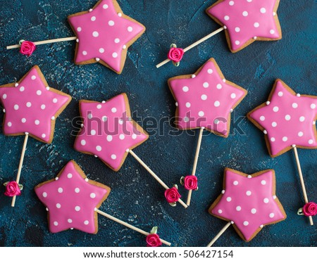 Homemade gingerbreads in the form of pink stars with dots (polka) on sticks on the dark blue background. Selective focus.