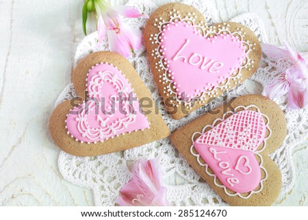Homemade gingerbreads in the shape of heart with pink and white frosting, patterns and an inscription Love on the wooden table. Space for text and selective focus. - stock photo