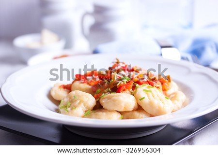 Homemade gnocchi with vegetable sauce and cheese - stock photo