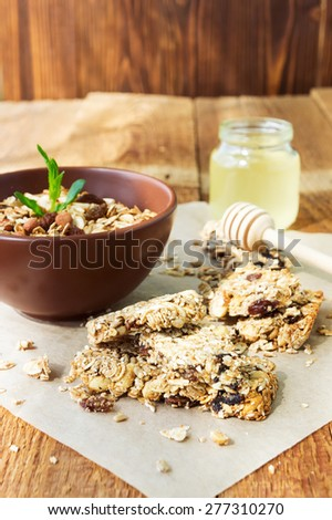 Homemade granola bars with dried fruits and nuts, a jar of honey and a bowl of granola on vintage wooden background - stock photo