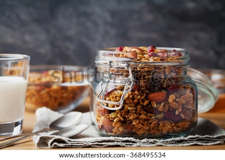 Homemade granola in jar on rustic kitchen table, healthy breakfast of oatmeal muesli, nuts, seeds and dried fruit - stock photo