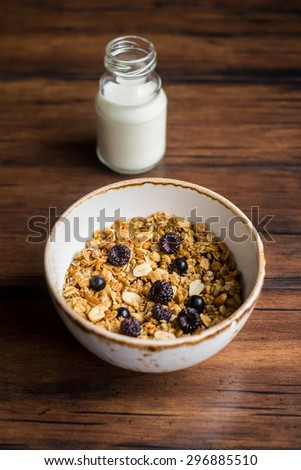 Homemade granola or muesli with oat flakes, corn flakes, dried fruits and toasted peanuts with fresh berries in a bowl and a bottle of fresh milk for breakfast, selective focus - stock photo