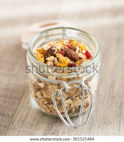 Homemade granola or muesli with oat flakes, dried cranberry, cherry, apricots, goji berries, toasted almonds and peanuts in a jar for breakfast or healthy snack, selective focus - stock photo