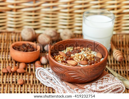 Homemade granola with nuts, raisins and seeds in a ceramic bowl for a healthy Breakfast.  Rustic style. Selective focus