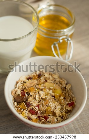 Homemade granola with oat flakes, honey, brown sugar, nuts and dried fruits in a bowl with a jar of fresh honey and a glass of milk, selective focus - stock photo