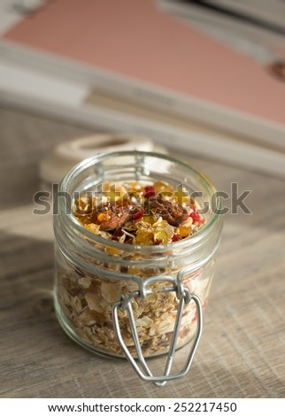 Homemade granola with oat flakes, honey, brown sugar, nuts and dried fruits in a jar, selective focus - stock photo