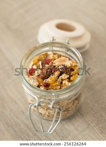 Homemade granola with oats, toasted nuts, dried cherry and honey in a jar, selective focus - stock photo
