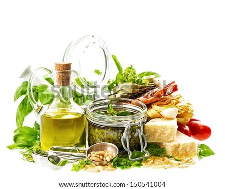 Homemade green pesto sauce and ingredients on white background. Olive oil, basil, parmesan, pine nuts, tomato. Food background.  - stock photo
