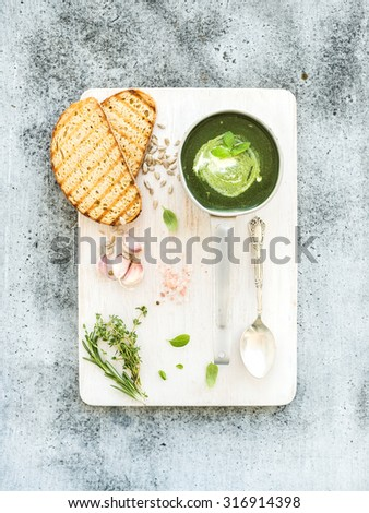 Homemade green spinach soup in a metal scoop with grilled bread slices, herbs, spices on white wooden  serving board over grunge grey background, top view - stock photo