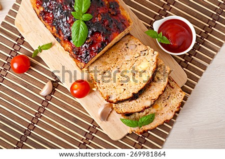 Homemade ground meatloaf with ketchup and basil.Top view - stock photo