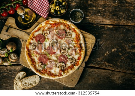Homemade ham, salami and mushroom pizza served on a board on an old rustic wooden kitchen table surrounded by the fresh ingredients from the recipe, overhead view with copyspace - stock photo