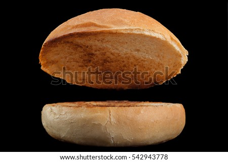 Homemade hamburger bun with fried surface on black background