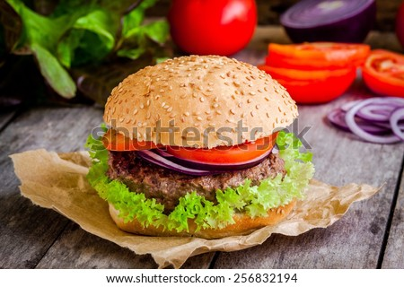 homemade hamburger close up with fresh green lettuce, tomato and red onion on rustic background - stock photo