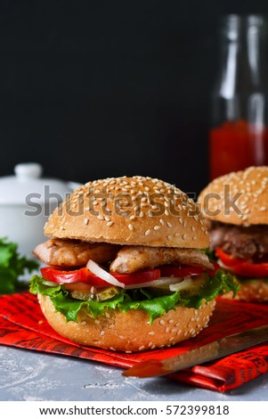 Homemade hamburger with beef, tomatoes and lettuce on a concrete background. Fast food.