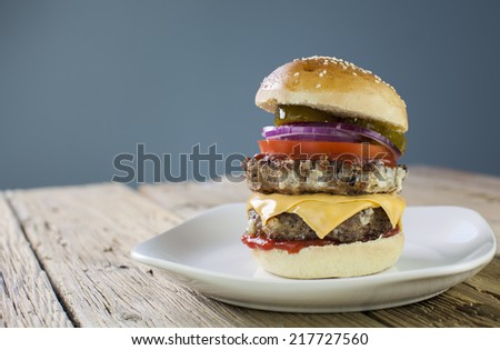 homemade hamburger with fresh vegetables on a wood table - stock photo