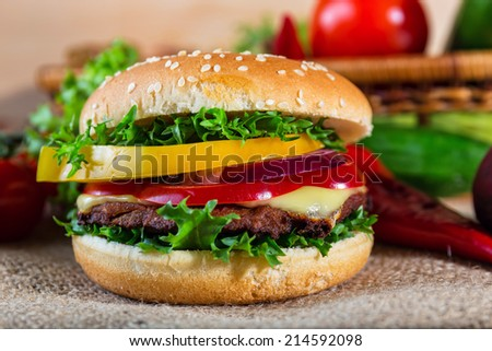 homemade hamburger with fresh vegetables on cutting board - stock photo