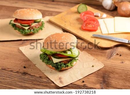 Homemade hamburgers with cheese, tomatoes and cucumbers - stock photo