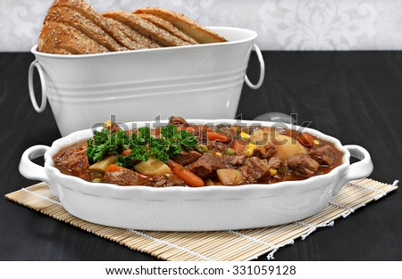 Homemade, healthy beef stew in an oval white casserole.  Italian bread as a side.