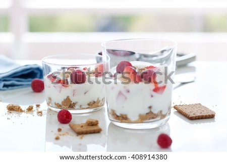 Homemade healthy dessert in glass with yogurt, fresh fruits and cookies for breakfast, horizontal, closeup
