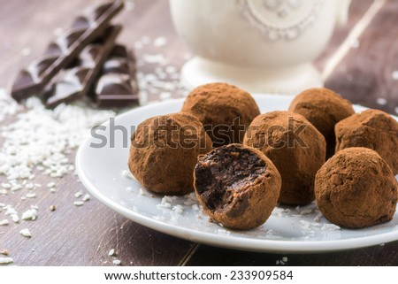 Homemade healthy vegan chocolate truffles with dates, coconut flakes and rolled oats served on white plate - stock photo