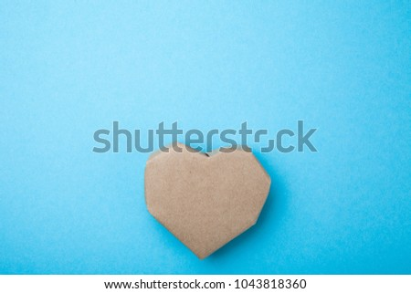 Homemade heart made from recycled paper on a blue background, empty space for text.