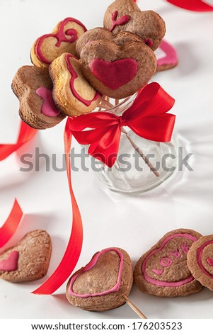 Homemade heart shape cookies on a stick in a glass.