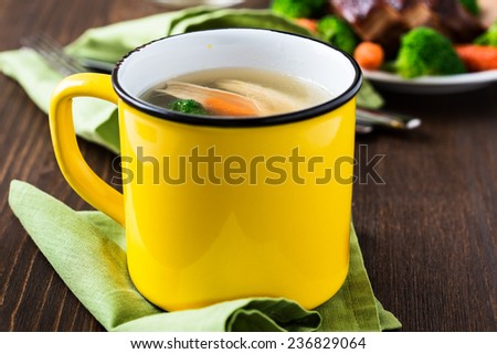 Homemade hot chicken soup in yellow mug for winter - stock photo