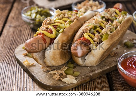 Homemade Hot Dog with fried onions and sauces on rustic wooden background - stock photo