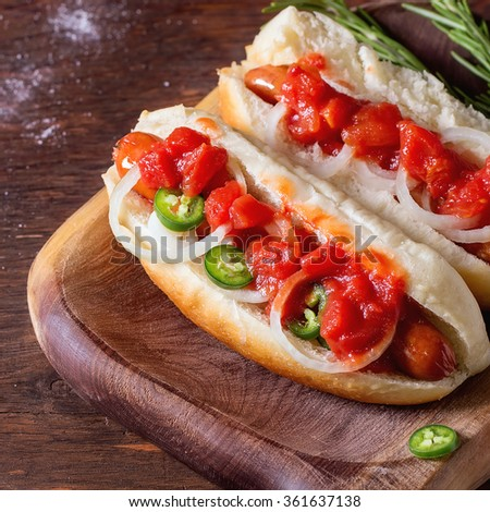 Homemade hot dogs on wooden plate with tomato sauce, onion, pepper and rosemary on wooden table. With copy space on left. Square image with selective focus - stock photo