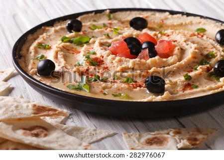 homemade hummus with olives and herbs on a plate close-up. horizontal