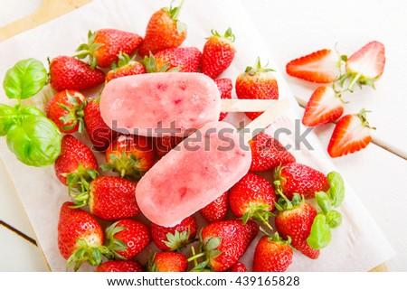 Homemade ice cream popsicles with fresh strawberries. Light organic summer dessert with ripe berries. - stock photo