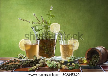 Homemade ice tea with lemon on a green background - stock photo