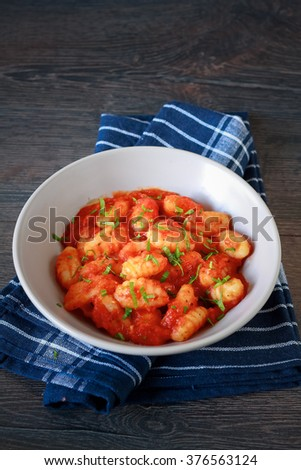 Homemade italian gnocchi with tomato sauce on a table - stock photo