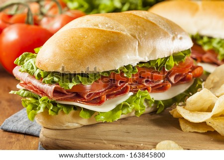 Homemade Italian Sub Sandwich with Salami, Tomato, and Lettuce - stock photo