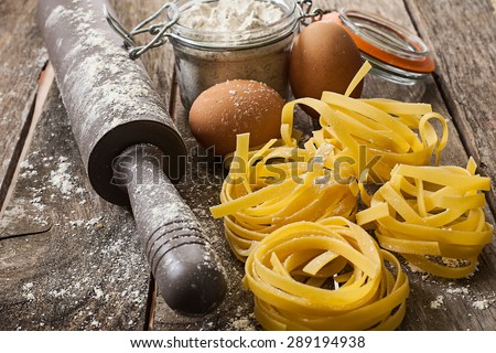 homemade italian tagliatelle on wood surface - stock photo