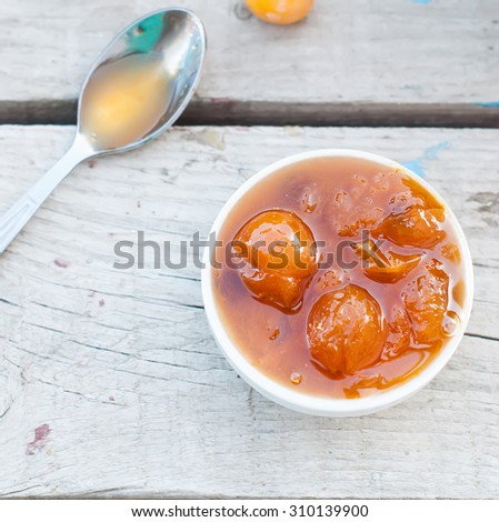 homemade jam of yellow plum, cherry plum in a colander and scattered on the table, a jar of jam on a white board, selective focus - stock photo