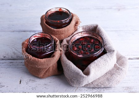 Homemade jars of fruits jam in burlap pouches on color wooden planks background - stock photo