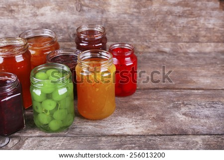 Homemade jars of fruits jam on rustic wooden background - stock photo